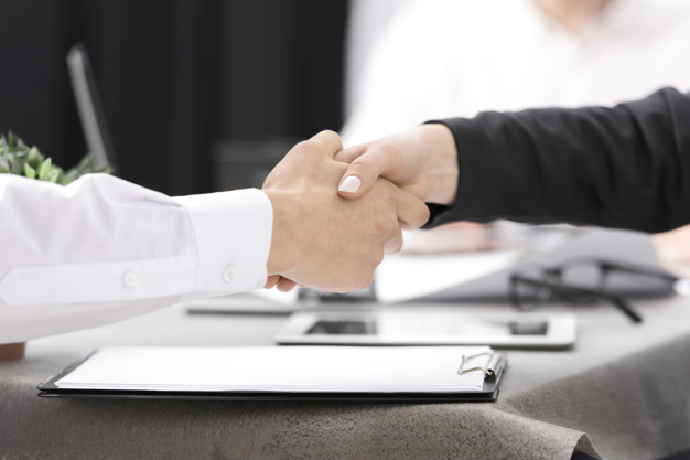 two-businesspeople-shaking-each-other-s-hand-clipboard-desk_23-2148073316